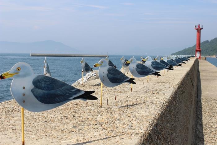 港に並ぶカモメは約300羽は木村崇人の「カモメの駐車場」。 風が吹くと一斉に向きをかえるカモメたち。穏やかな港の景色に溶け込んだ作品です。