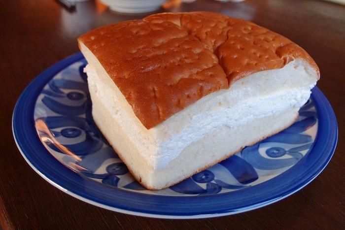 「牛乳パン」とは、牛乳を練り込んで焼き上げたパンを切り分け、クリームをサンドしたものです。  小松の「牛乳パン」の最大の特色は、何と言ってもクリームの量。一気に頬張ろうとすると、クリームがはみ出してしまうので、食べる時は切り分けて、片面のパンを剥がして、クリームをつけながらお上品に頂きましょう。