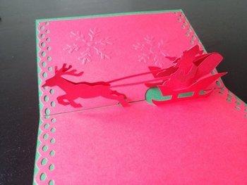 やはり、クリスマスこそ、華やかなポップアップカードがお似合い。楽しいクリスマスの始まりを告げるような、サンタとトナカイのポップアップカードです。表紙には、クリスマスをイメージさせるシルバーのリボンを飾って。