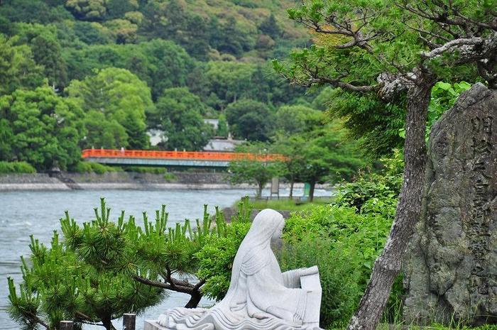 【宇治橋西詰からの宇治川の眺め。奥に見える橋は、宇治神社と宇治公園を結ぶ「朝霧橋」。画像手前は、『源氏物語』の作者・紫式部のモニュメント。】