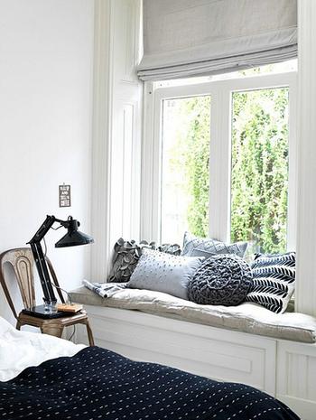 ベッドカバーをネイビーに。全て素材とデザインが異なるクッションも、色味を統一させればごちゃっとした印象を与えません。まどの外のグリーンも良いアクセントになっています。