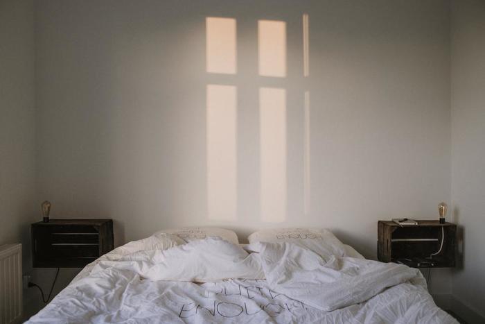 シンプルライフ。白いベッドシーツに包まれて、朝を気持ちよく迎えよう