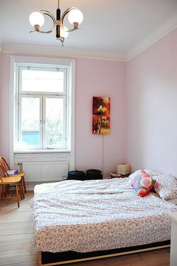 淡いピンクの壁に、小花模様のベッドカバー&クッションを配置。スイートになりすぎないよう、大胆な柄のクッションが良いアクセントに。
