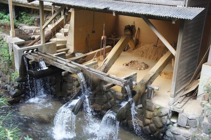 """大浦川の水力で陶土を挽く「唐臼(からうす)」。""""ししおどし""""のように、溜まった水が落ちる反動を利用して陶土をつきます。 静寂な里に響くのは、ぎーバッタンという唐臼の音。この唐臼の音は「残したい日本の音風景100選(1996年認定)」に選ばれています。"""
