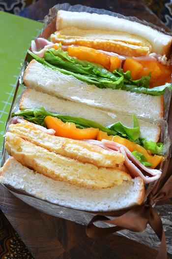 ふわふわのオムレツ、野菜、ハムと全部が入ったボリューム満点のサンドイッチ。大きな口で頬張りたい! オーブンペーパーなどでくるんでから半分にカットすると、食べやすいですよ。