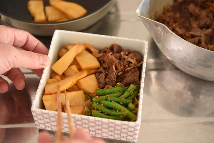 汁気のあるものは、詰める前にしっかり汁を切ったり、カップに入れたりするのは基本。でも、味が混ざっても問題ないものは無理に仕切らず、隣り合わせにすれば盛り付けやすくなります。例えば、今回の献立の「牛肉のしぐれ煮」と「たけのこのきんぴら」は一緒に食べても美味しいくらいなので隣同士に詰めましょう。