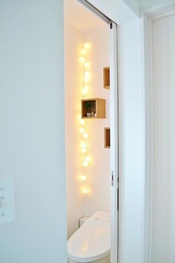 白で統一されたトイレにまんまるの間接照明と無印良品の棚を取り付けて。あたたかみのある光に心も癒されそう。