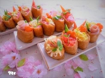 ハムをバラの花のように巻いたおしゃれないなり寿司。艶やかでまさにひな祭りにぴったり。出来合いのおいなりさんを使っているので手軽で、実は材料費もあまりかかっていないのも、助かります。