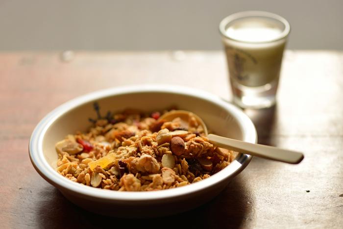 """押し麦にした燕麦(えんばく)を主として、ライ麦や玄米といった穀物加工品、油脂を加えてオーブンで焼き上げた""""グラノーラ""""は、ビタミンや繊維質が豊富な健康食品。プレーンなタイプのものから、蜂蜜などで甘味をつけたもの、またドライフルーツやナッツを加えたもの等種類も豊富で、様々なタイプのグラノーラ製品が各社から販売されています。"""