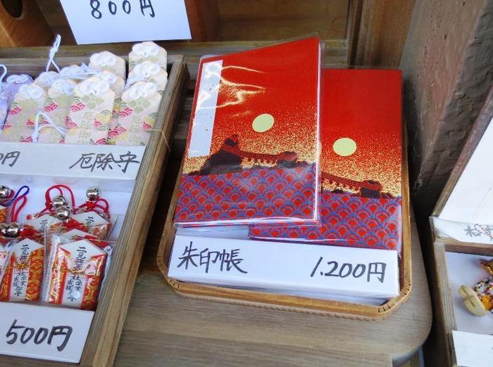 三重県伊勢市・二見興玉神社の御朱印帳にはデザインが2種類あります。こちらは赤色の「日の出」。本殿の裏手の鳥居から拝める夫婦岩が日の出と共にデザインされています。美しい風景が印象的。