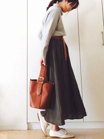 こちらは、こげ茶の小物でまとめた上級コーデ。こげ茶のレザーバケツ型バッグ、大きめのピアス、ベルトが素敵なアクセントに。靴は白で軽やかにしているのも真似したいポイントです。