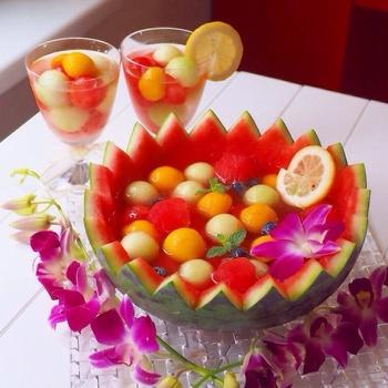 すいかを器にした、すいかのフルーツポンチ☆すいかは丸くくり抜き、残りのすいかで作ったスイカ氷と、同じように丸くくり抜いたメロンやマンゴーなどのフルーツを一緒に加えて盛るだけ!見た目も豪華で、パーティーなどにも最適です。