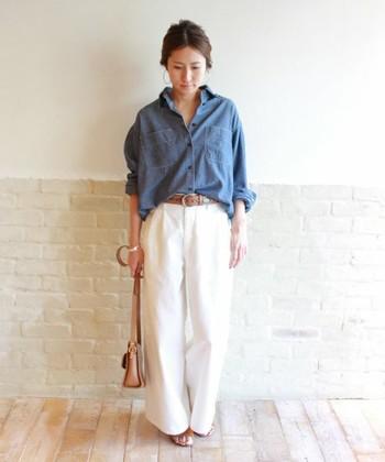 シンプルなデニムシャツ×ホワイトのワイドパンツ。フォークロア調のベルトやサンダル、ショルダーバッグという小物がポイントになったスタイルです。
