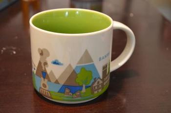 お隣の国カナダにも、バンクーバーなど主要都市のご当地マグカップが用意されています。  こちらはカナディアン・ロッキー山脈観光の中心地であるBANFF(バンフ)のカップ。高い山のや木、山小屋などの絵柄が見えます。