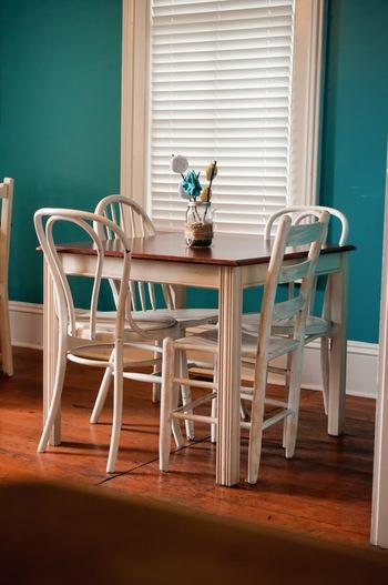 シャビーなダイニングチェアとアンティーク調のテーブル。南仏風の鮮やかなブルーの壁紙も素敵です。