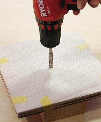 木材の中心になる部分に鉛筆で印をつけます。木材を2枚重ねて、マスキングテープでずれないように固定したら、電動ドリルで中心に穴をあけます。