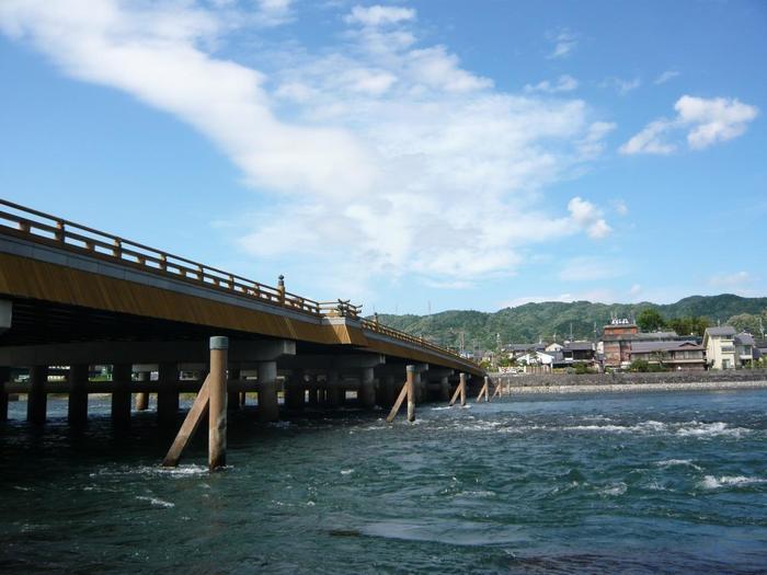 """京阪宇治駅のすぐ目の前に伸びる「宇治橋」は、歴史的な趣きを色濃く残す橋で、""""日本三古橋""""の一つとして良く知られています。  大化2(646)年(奈良期)に架橋されたと伝わりますが、戦乱や洪水によって幾度も流失し、交通の要衝として機能してきた「宇治橋」は、その度に再生してきました。現在架かる橋は、平成8(1996)年に架けかえられたもので、橋の構造自体は、コンクリート製ではあるものの、周囲の自然景観、歴史的背景を踏まえて、木材を巧みに用い、伝統様式の木造橋のように仕上げられています。  宇治橋の中で、最も特徴的なのが中央部の「三ノ間」と呼ばれる、外側に張り出した部分です。この「三ノ間」には、かつて橋の守護神「橋姫」が祀られた「橋姫神社」がありました。(現在「橋姫神社」は、宇治川西側のあがた通り沿い「辻利一本店」隣に鎮座する)。  三の間から汲みあげた汲みあげた水は、""""宇治川の名水""""として茶人らに愛され、現在も毎年10月第一日曜日には「名水汲みあげの儀」が行われています。"""