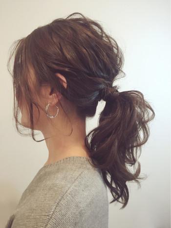 髪全体をウェーブ風に巻いたらざっくりまとめて少しだけ髪を引き抜いて、結び目に巻き付ければ完成のローポニー。 低めの位置で結ぶのが大人っぽく仕上げるポイントです。