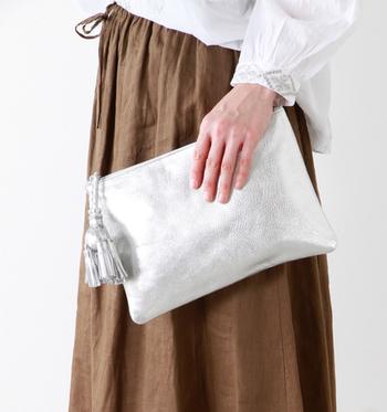 タッセルがアクセントのモードなクラッチバッグ。光沢のあるレザー素材がリッチ感をプラスしています。アクセサリーを身に着ける感覚で持ちたいアイテム!