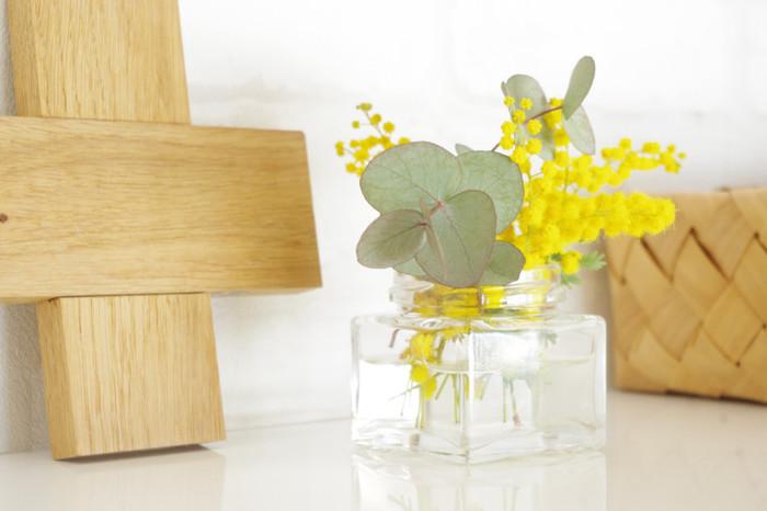 春の風を感じるミモザにやさしいユーカリのグリーンはぴったり。すっきりとした四角いガラスの器と丸いミモザとユーカリが対照的ですね。