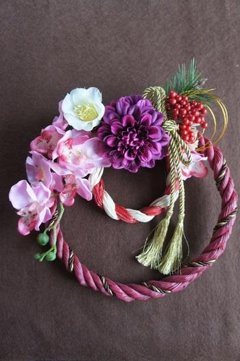 ワインレッドカラーの縄と紅白の小さなしめ縄の組み合わせだけでも存在感がありますね。そこに華やかな花が加わってより一層おめでたい雰囲気が楽しめるリースです。