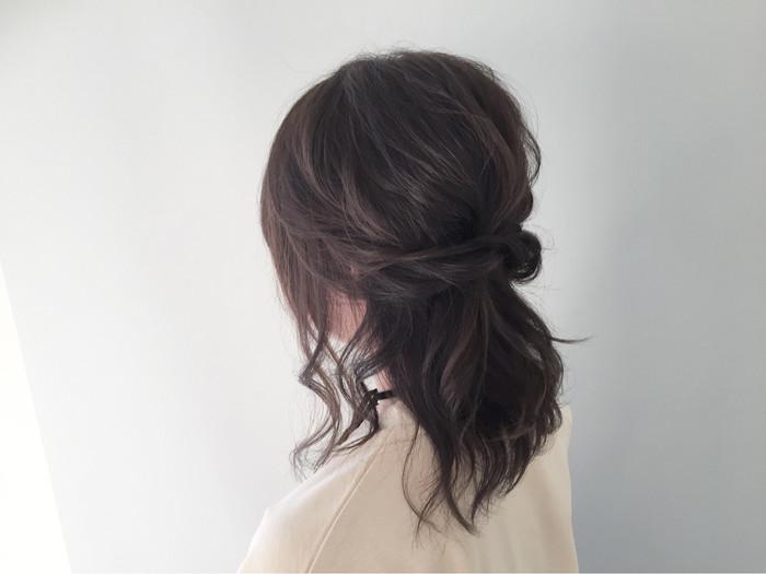 やや太めのアイロンで髪を巻いてねじり、ハーフアップに。髪の広がりをナチュラルに防いでくれます。