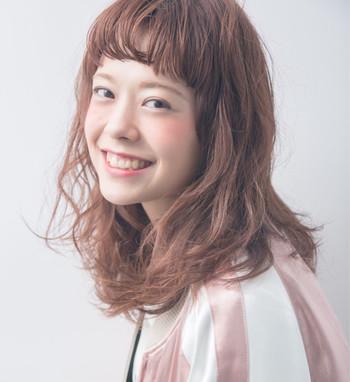 ピンク系のヘアカラーに柔らかい印象のパーマヘアも、眉上ラウンド前髪で、スタイリッシュな印象に。ボーイッシュな着こなしにも似合いそうです。