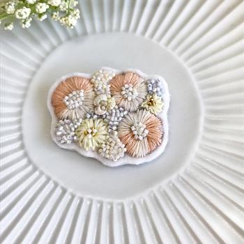 優しいオレンジのお花を取り囲むようにちりばめられたビーズが春らしい。刺繍糸で表現した花びらの絶妙なグラデーションは、自然が織りなすそれのよう。ぱっと目をひく存在感は、コーデのアクセントとして活躍してくれます。
