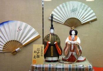 こちらは「 江戸木目込人形(えどきめこみにんぎょう)」。江戸木目込人形は京都で作られる人形に比べると、細面ではっきりした顔立ちが特徴だそうです。  ちなみに、人形の後ろに飾られているのは「江戸扇子」です。伝統工芸品としての指定は受けていないものの、伝統的技法で作られています。