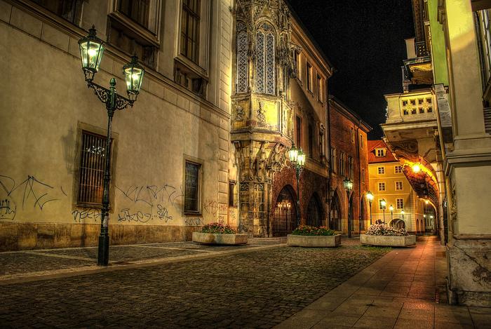 プラハ歴史地区は夜になると異なる魅力を見せてくれます。街燈と窓から漏れる灯りが歴史ある建造物をやさしく照らします。
