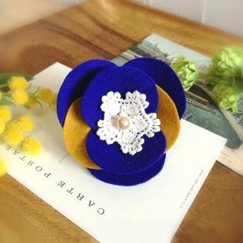 フェルトを切って重ねて作るお花のコサージュ。真ん中のレースがいいアクセントになっています。色合いを変えていろいろなフェルトコサージュを作ってみたくなりますね。