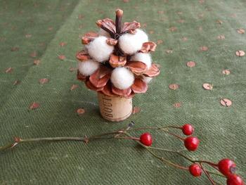 松ぼっくりのミニツリーの土台にはコルクを使用。ナチュラルなツリーに、赤い実がとっても素敵。