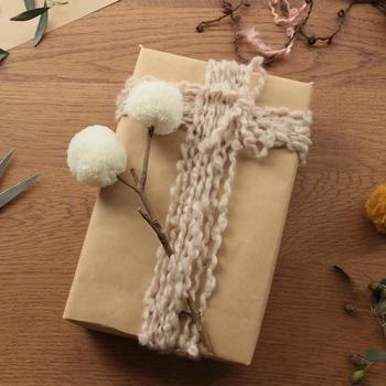 枝の先に綿毛…と思いきや、こちらは毛糸で作ったポンポン。カールした毛糸を巻き付ければ、温もりあるラッピングのできあがり! ごちゃごちゃしがちなデコレーションも、トーンを合わせるとこんなに落ち着いた印象に。
