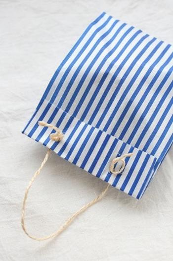 持ち手のない袋に穴をあけて紐を通してみましょう。簡単に持ち手つきのバッグができますよ。