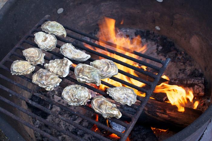 牡蠣を焼いて。殻の中の牡蠣にグラタン生地を入れて、そのまま焚き火の炭火でじっくり焼くのもおすすめです。