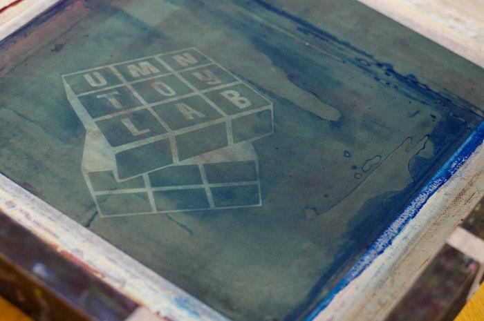 刺繍枠にスクリーンになる布をセットしたら、インクを通したくない部分にモッドポッジを筆で塗って原版を作成します。 原版の作り方は様々ですが、たとえば下絵を鉛筆やマジックでなぞって写す方法や、プリントしたい図柄の紙を切り抜いてスクリーンの上に置いてモッドポッジを塗り、図案をかたどる方法などがあります。