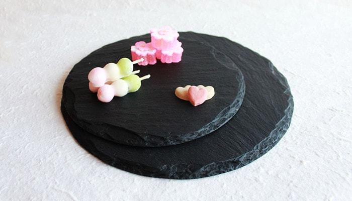 硯に使われる石で作ったプレートは、文様の出方にひとつひとつ違いがあってとても表情が豊かです。小さな和菓子が輝きます。