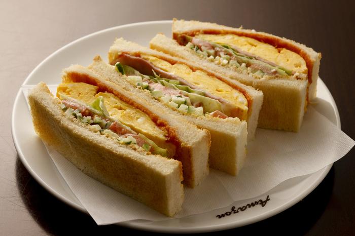 七条駅近くにある「喫茶アマゾン」は、1972年創業の老舗喫茶店。絶品のサンドイッチが頂けることで良く知られています。  【画像は、人気の「ミックストースト」ハーフサイズ。香ばしく焼かれたトーストには、フワフワの卵焼き・ハム・トマト・きゅうりがサンドされています。ボリューミィで絶品。】