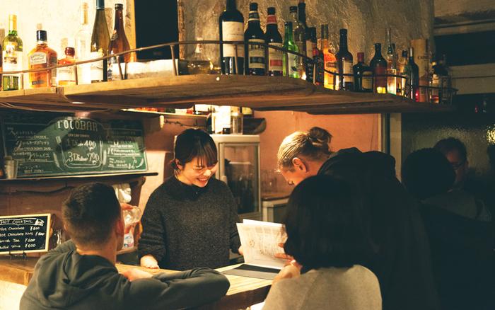 夜にはリビングが一般開放され、ふらりと立ち寄れるバーに。 宿泊客でなくても利用が可能なので、近所に住んでいる方から外国からのゲストさんまで、お酒を飲みながら気軽にお話できる雰囲気です。メニューはビールやカクテルに加えて、日本のお酒やおつまみも楽しめます。
