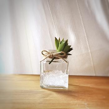 びんの口に結んだ麻ひもに、グリーンを差し込んで。 写真は100円均一の造花ですが、いい香りのするハーブなどを使うのもおすすめです。