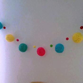 毛糸をボールに巻いて作ったガーランドは、壁面のアクセントに。カラフルな毛糸玉と小さなポンポンを組合せたガーランドは、子ども部屋のインテリアにピッタリ◎