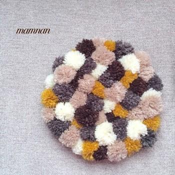 小さなサイズのポンポンを、ぎっしり並べて縫い合わせたチェアマット。モコモコのぽんぽんマットは、木製チェアに似合いそう。