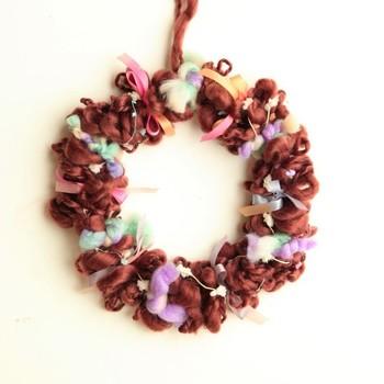 もこもこの毛糸にリボンを巻きつけたクリスマスリース。毛糸やリボンの質感の違いを活かしたリースは、カラーを変えれば、クリスマス以外でも玄関のアクセントにもなります。