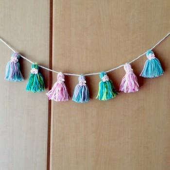 ミックスカラーの毛糸のタッセルを、等間隔でヒモで繋いだガーランド。タッセルの根本をまとめる糸に小さな花を添えてあるので、シンプルなお部屋も華やかになります♪