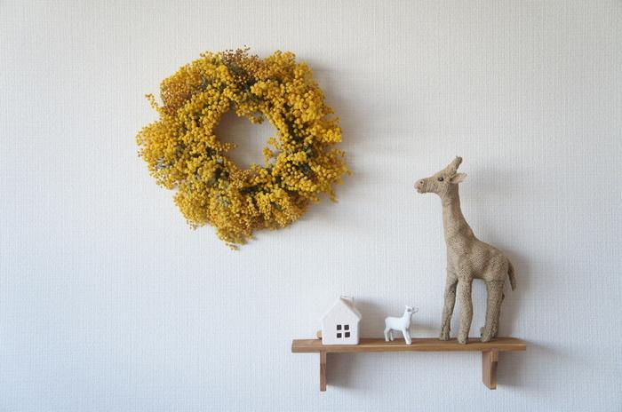 白い壁に映える、ドライフラワーのミモザのリース。飾るだけで、シンプルな部屋がおしゃれに変身。