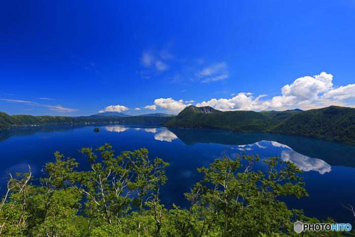 人を寄せ付けない神秘的な魅力を持つ摩周湖は、高さ300メートルから400メートルの断崖に囲まれています。波一つ無い静かな水面が、鏡のように周囲の断崖を映し出す幻想的な景色は、美しいだけでなく、畏怖さえも感じるほどです。