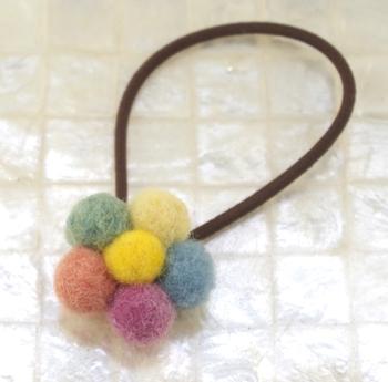 練習などでたまったフェルトボールを集めて、こんなヘアゴムはいかが?お花が咲いたようできれいですね。色のトーンも落ち着いているので、大人の女性もさりげなく付けられそう。