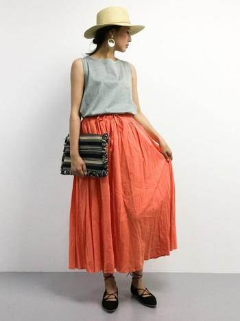 綺麗なオレンジ色のギャザースカートには、他のアイテムを落ち着いたカラーでまとめて。クラッチバッグや、編み上げのフラットパンプスなど、小物使いで大人なエキゾチックに。