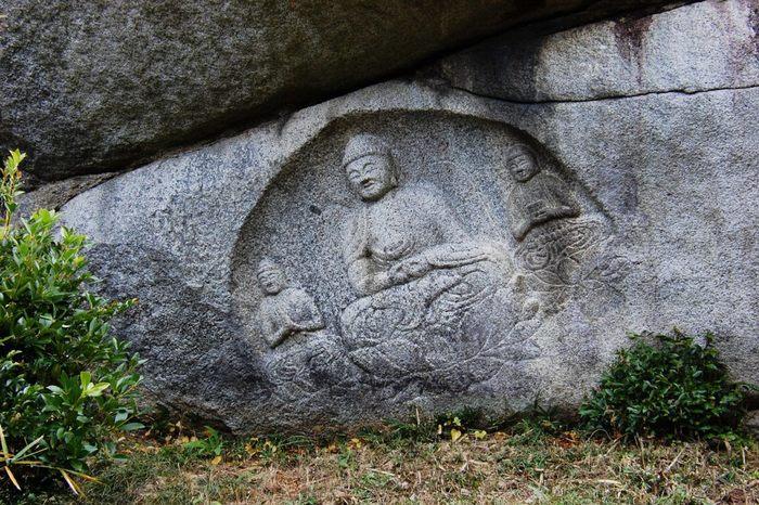"""当尾地区は、古くから南都仏教の文化を色濃く残すエリアです。ハイキングコース途上には、寺院や修行場がある他、多くの石仏が散在しています。古刹や石仏、初夏の緑や里山の雰囲気を味わいながら、里山散策ができます。  【画像は、石仏の中で最も知られる""""わらいぼとけ""""。観世音菩薩坐像と阿弥陀如来坐像、勢至菩薩(せいしぼさつ)坐像の「阿弥陀三尊磨崖像」です。】"""