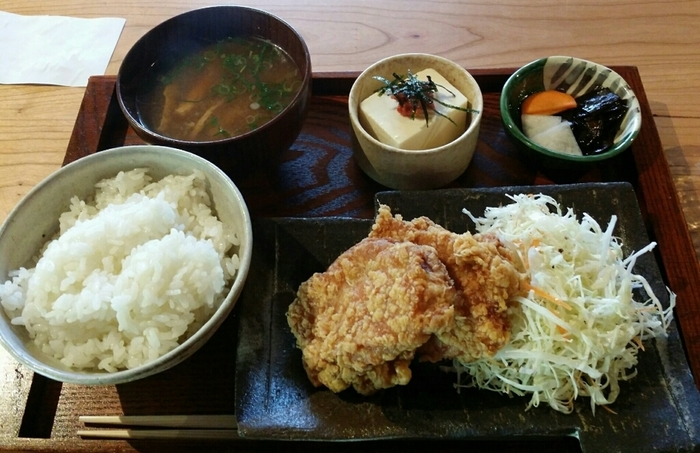 鳥名子名物『鴨すき』や『京地どりの天ぷら』等、丹波・福知山産の食材を用いた料理が楽しめる「柳町」。日本酒やワイン、カクテル等と鳥料理を頂くお店ですが、ランチ時なら、リーズナブルに美味しい鳥料理や蕎麦が味わえます。 【画像は「唐揚げ定食」。唐揚げは、もちろん揚げたて熱々。ジューシーでボリューミーと人気。地元産の米を炊いたご飯はお代わり自由。食後には果物も付いてきます。】